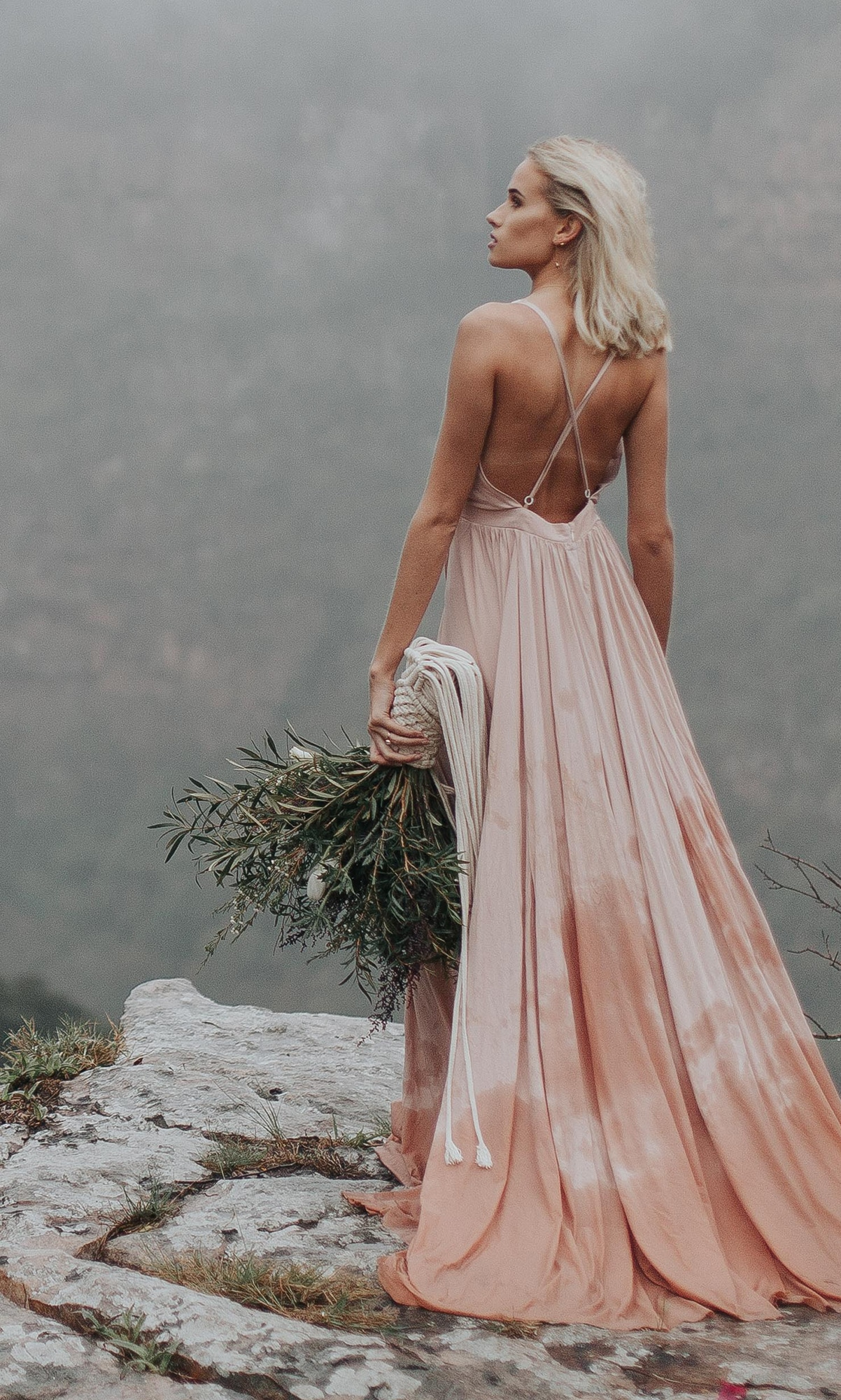 Oh Happy Day striking boho bride with blush dress and exposed back holding natural greenery bouquet
