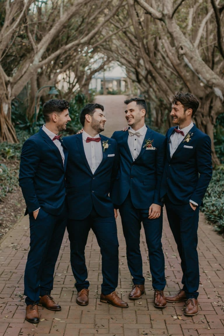 groomsmen-in-navy-suits-and-red-bowties