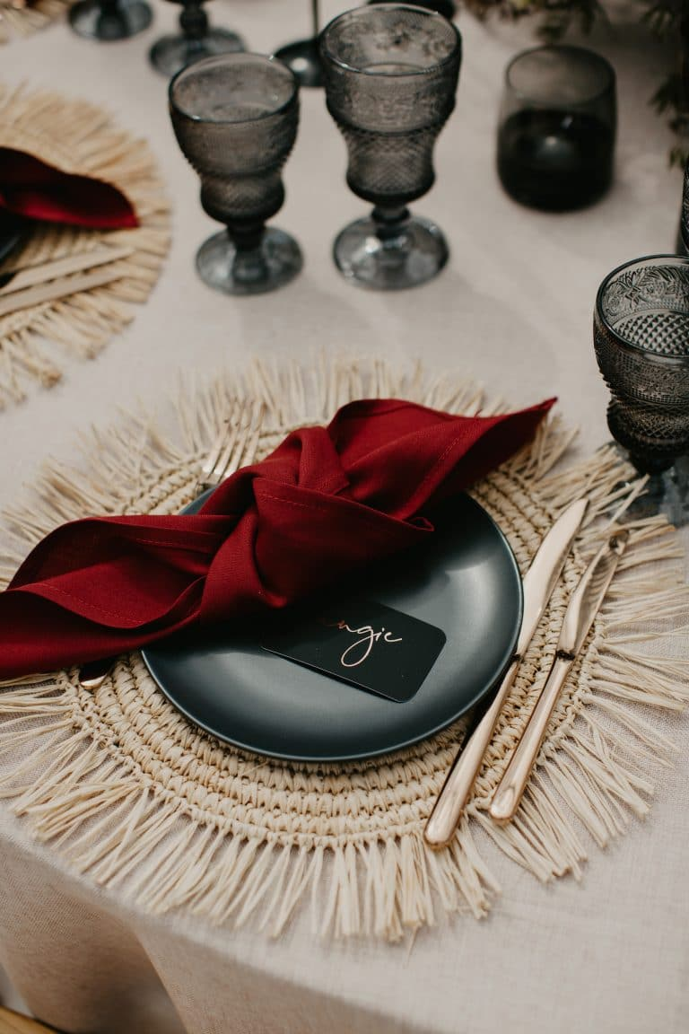 place-setting-with-black-plate-and-ruby-red-napkin