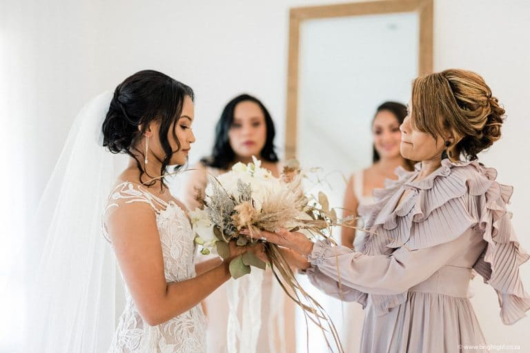 bride receiving bouquet from mother