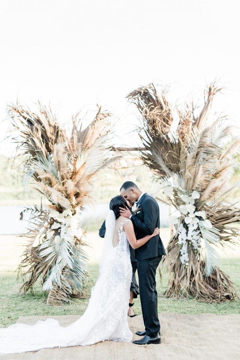 outdoor wedding ceremony with boho dried floral arch