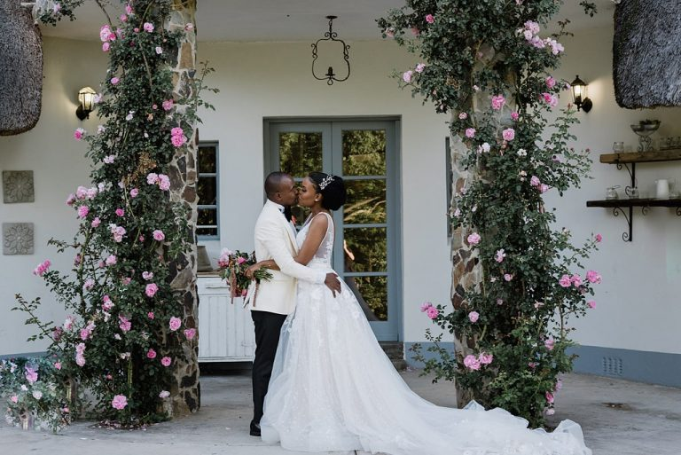 couple kissing under floral arch